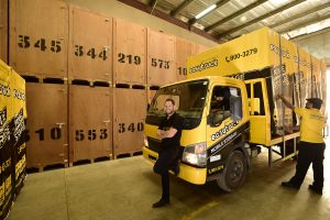 Easytruck staff offloaing yellow Easytruck mobile pods